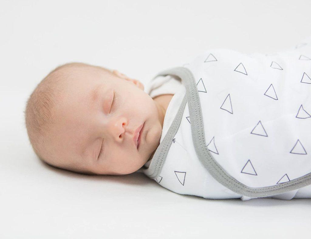Baby in weißem Pucksack mit grauen Dreiecken