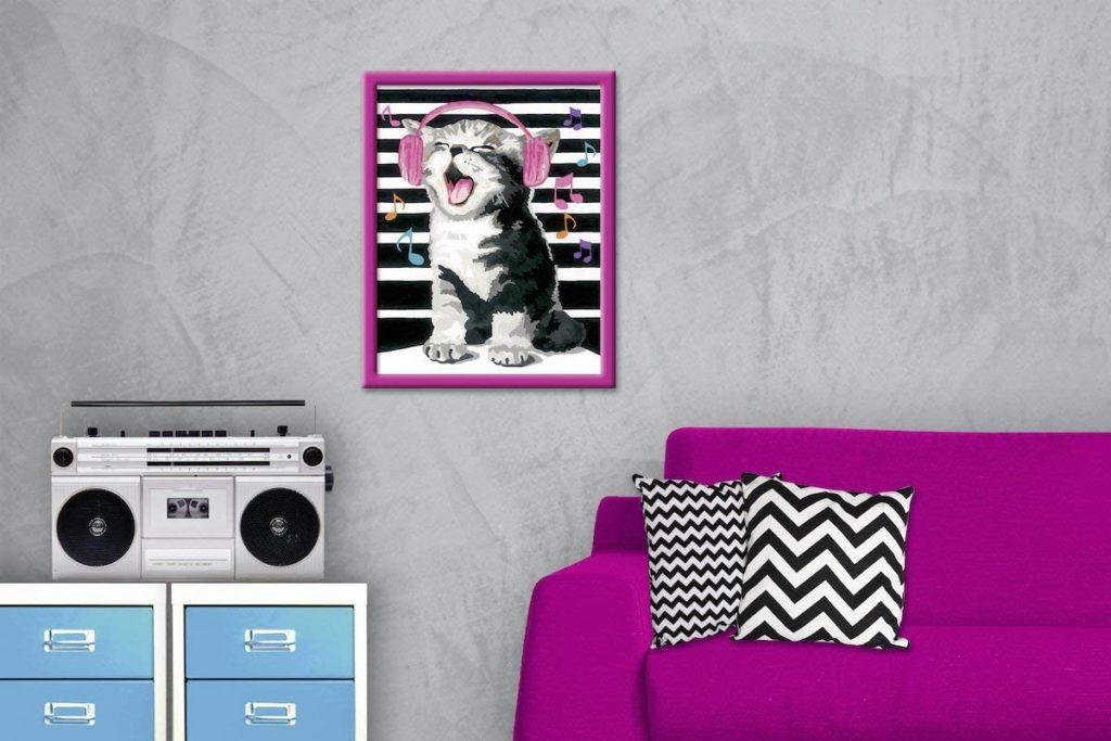 Ausgemalte Malen nach Zahlen Vorlage mit singender Katze hängt an grauer Wand