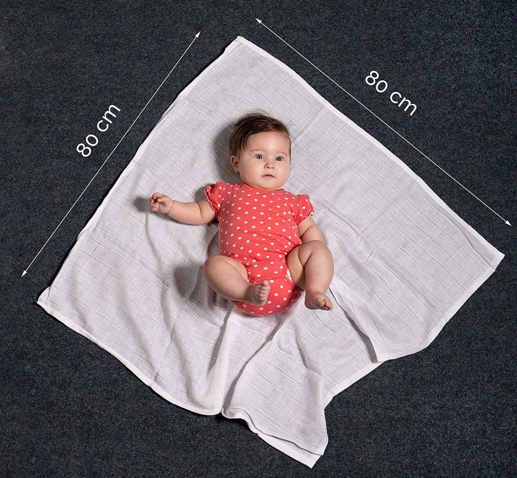 Baby liegt auf weißem Mulltuch. Abmessungen von Mulltuch